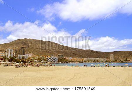 Los Cristianos beach Tenerife Canary Islands Spain Europe - June 13 2016: Tourists on the beach enjoying the sun