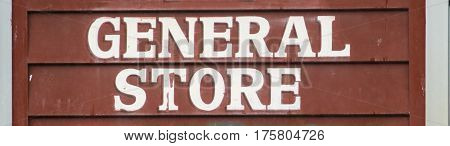 Old style General store sign on rustic brown clapboard wall.