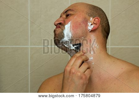 Man shaving his face with the razor blade through shave foam. Men skin care concept. Bald