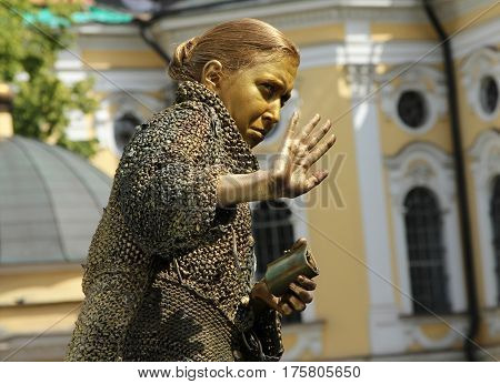 St. Petersburg, Russia - Jul 5, 2014: Street Actress (living Statue) In The Image Of A Greedy Old Wo