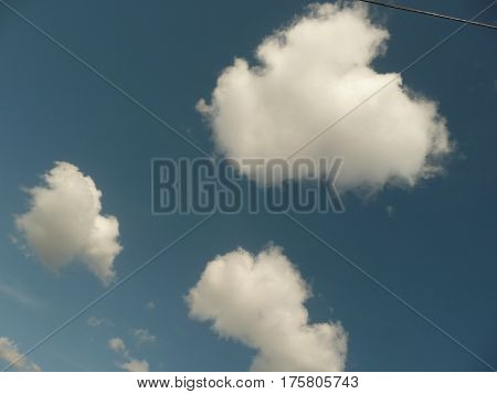 A trio of large fluffy clouds look pearlescent against a dark blue sky