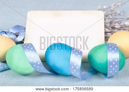 Painted eggs lovely polka dot ribbon willow twigs and retro card as a field for your text on blue fabric tablecloth. Soft light Easter background pastel shades. Close shot.