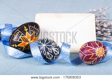 Hand painted eggs in ethnic style lovely polka dot ribbon willow twigs and retro card as space for your text on blue fabric tablecloth. Soft light Easter background. Close shot.