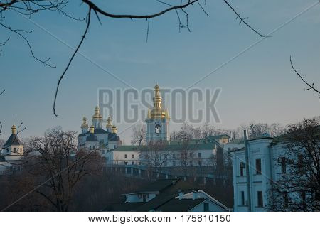 A green dome with a golden cross on the territory of the Kiev-Pechersk Lavra against the backdrop of the city in smog