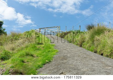 Typical wooden farm gate at top of rise and end of path.