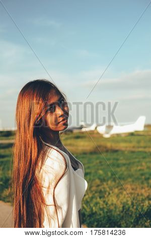 Beautiful female portrait on the airfield late afternoon