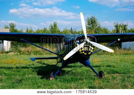Propeller of the blue airplane on the grass of airfield