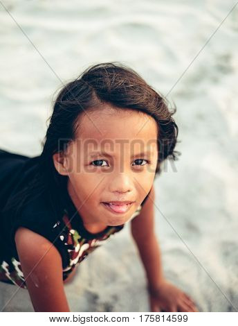 Playful little girl on the beach crawling on the sand