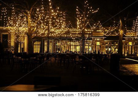 empty night restaurant, lot of tables and chairs with noone, magic fairy lights on trees like christmas celebration close up