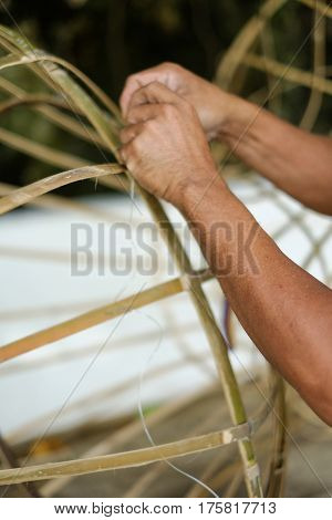 Man making object from bamboo by hand