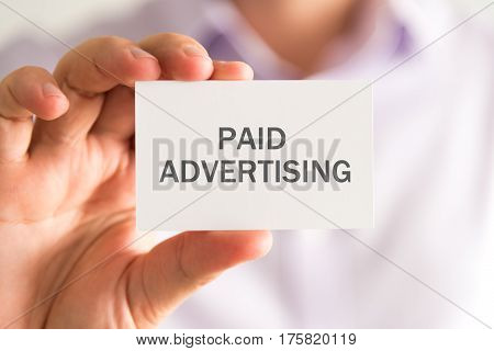 Businessman Holding A Card With Paid Advertising Message