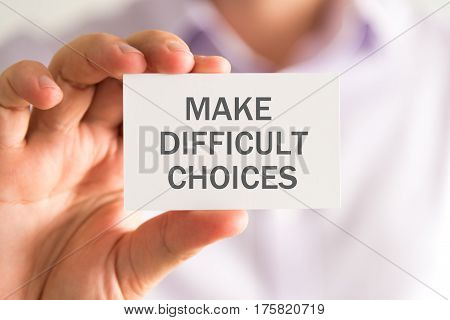 Businessman Holding A Card With Make Difficult Choices Message