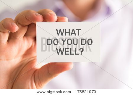 Businessman Holding A Card With What Do You Do Well ? Message