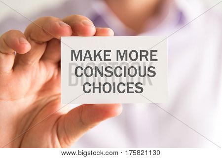 Businessman Holding A Card With Make More Conscious Choices Message