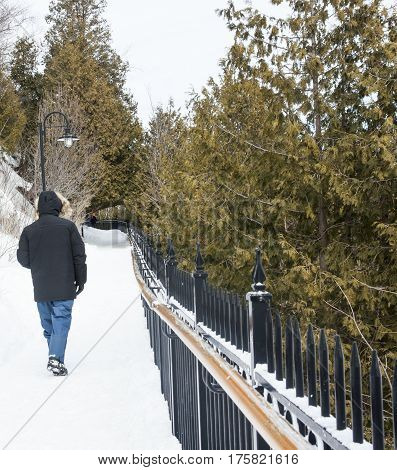 A man walking on a clear snowy path in Canada