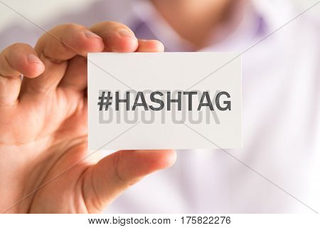 Businessman Holding A Card With #hashtag Message
