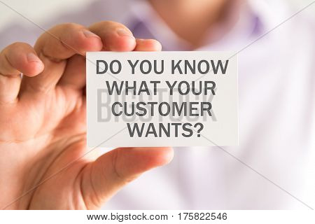 Businessman Holding A Card With Do You Know What Your Customer Wants ? Message