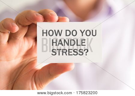 Businessman Holding A Card With How Do You Handle Stress ? Message