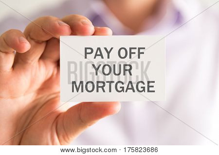 Businessman Holding A Card With Pay Off Your Mortgage Message