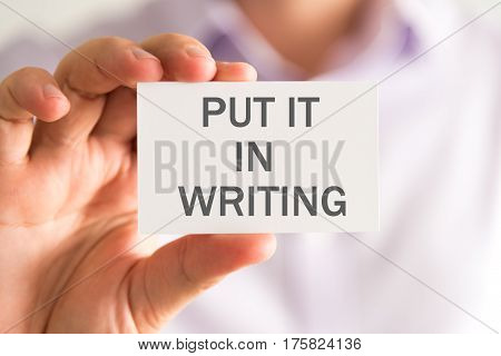 Businessman Holding A Card With Put It In Writing Message