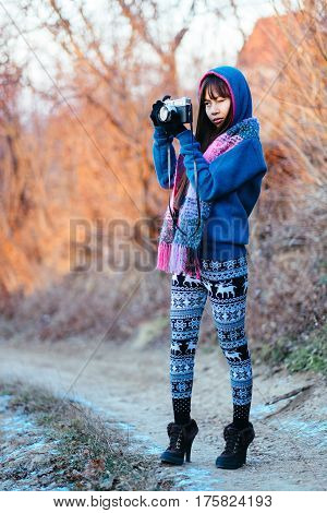 Girl outside in a cold weather photographing during the  sunset