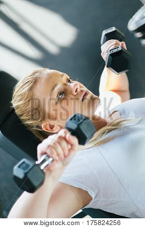 Young beginner girl exercising in the gym