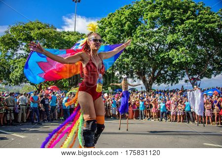 RIO DE JANEIRO, BRAZIL - FEBRUARY 28, 2017: Woman in the costume of firebird with feathers and wings walking on stilts in support of feminism at Bloco Orquestra Voadora, Carnaval 2017