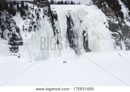 People walking on a frozen waterfall in Quebec City, Canada