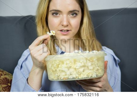 Young pretty blond caucasian woman with light brown eyes sitting on sofa eating popcorn. She is watching a movie at home and wearing smart clothes.