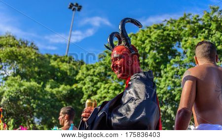 RIO DE JANEIRO, BRAZIL - FEBRUARY 28, 2017: Smiling young man in a costume of devil with red face, big black horns and black and red cloak walking on stilts at Bloco Orquestra Voadora, Carnaval 2017