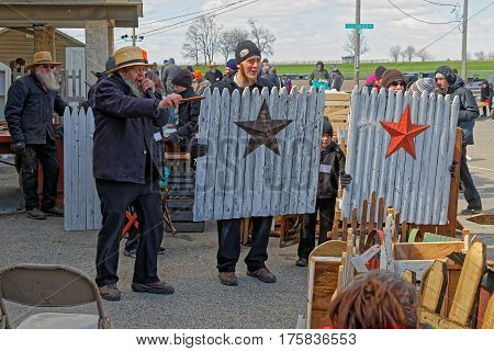 GORDONVILLE PENNSYLVANIA - March 11 2017: An Amish auctioneer volunteers at the annual spring auction `Amish Mud Sale` to benefit the Fire Company. Sale items include quilts antiques crafts food sporting goods tools farm equipment and horses.