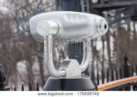 Side view of a coin operated binoculars agains a winter landscape