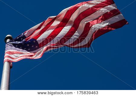 A U.S. flag unfurls from flagpole as wind blows.