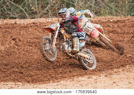 MONROE, GA - DECEMBER 2016:  A rider pops a wheelie while accelerating out of a turn in a motocross race at the Scrubndirt Track in Monroe GA on December 3 2016.