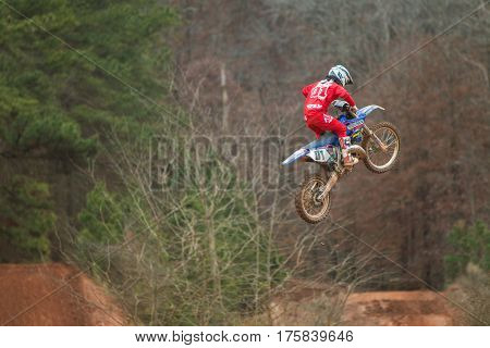 MONROE, GA - DECEMBER 2016: A rider gets airborne on a grey winter day after going over a jump in a motocross race at the Scrubndirt Track in Monroe GA on December 3 2016.