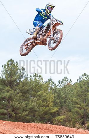 MONROE, GA - DECEMBER 2016:  A rider gets airborne after going over a jump in a motocross race at the Scrubndirt Track in Monroe GA on December 3 2016.