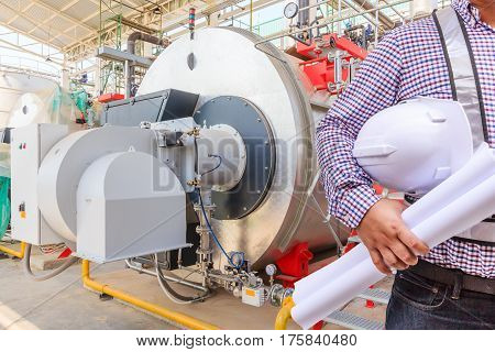 Young engineer holding helmet safety and blueprints working with gas boiler of heating system equipment in a boiler room