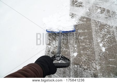 man hand holding snow shovel removing snow on the driveway