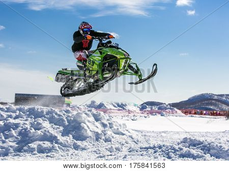 snowmobile rider jumping through white snow .