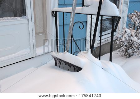 shovel buried by snow outside front door after blizzard