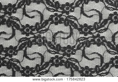 Black lace textile on a white background