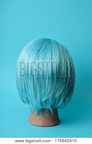 closeup of a blue wig in a mannequin head on a blue background