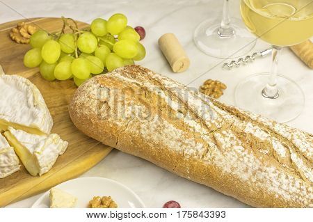 A loaf of white bread with soft cheese, grapes, and glasses of wine