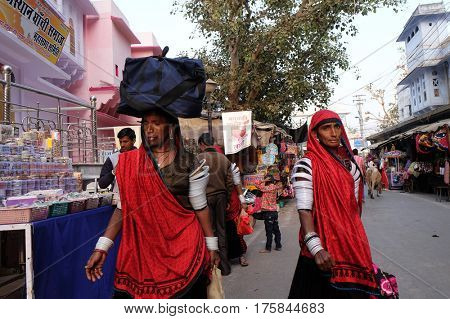 PUSHKAR, INDIA - FEBRUARY 17: Indian women with traditional colored sari on the street of Pushkar, Rajasthan, India on February 17, 2016.