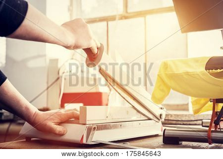 Man using manual paper cutter. Manufacture work.