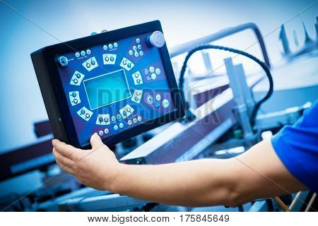 Worker programming print screening machine on the monitor. Industrial printer. Manufacture work.