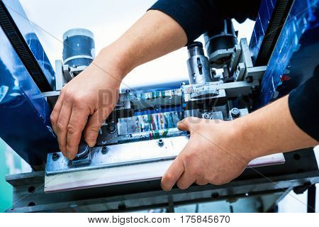 Worker preparing print screening metal machine. Industrial printer. Manufacture work.
