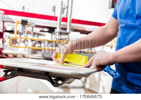 Man preparing material for screen printing in a workshop. Serigraphy industry. Manufacture work.