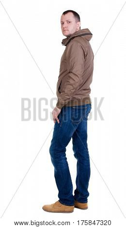 Back view of handsome man in brown windcheater looking up.   Standing young guy in jeans. Rear view people collection.  backside view of person.  Isolated over white background.