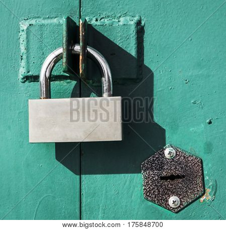 Padlock, new metal padlock on green background, security, metal door, door with two locks